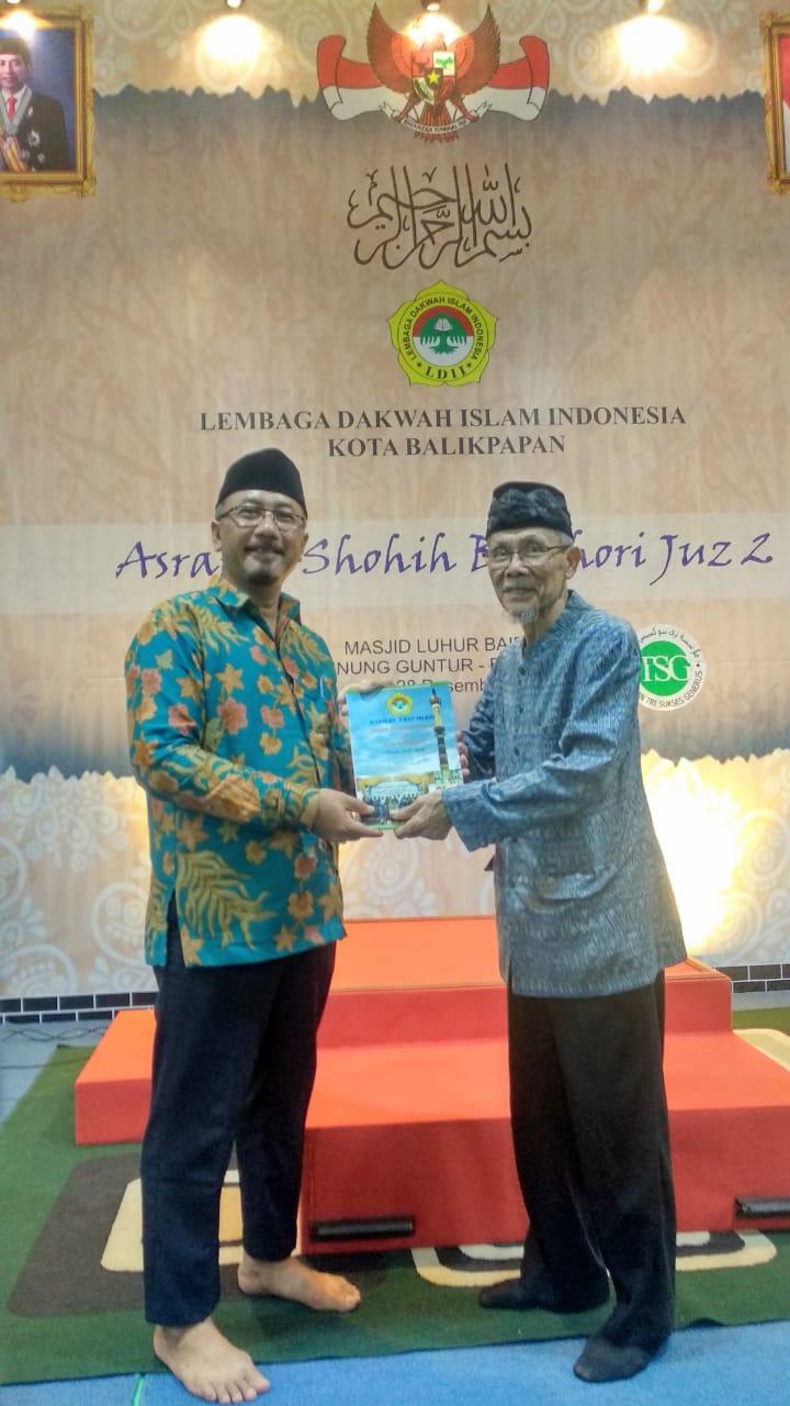 Ketua PPG H Hasan Bisri S.Psi menyerahkan Jurnal Kegiatan LDII 2019 kepada Ketua FKUB Drs H Abdul Muis Abdullah. Foto: LINES