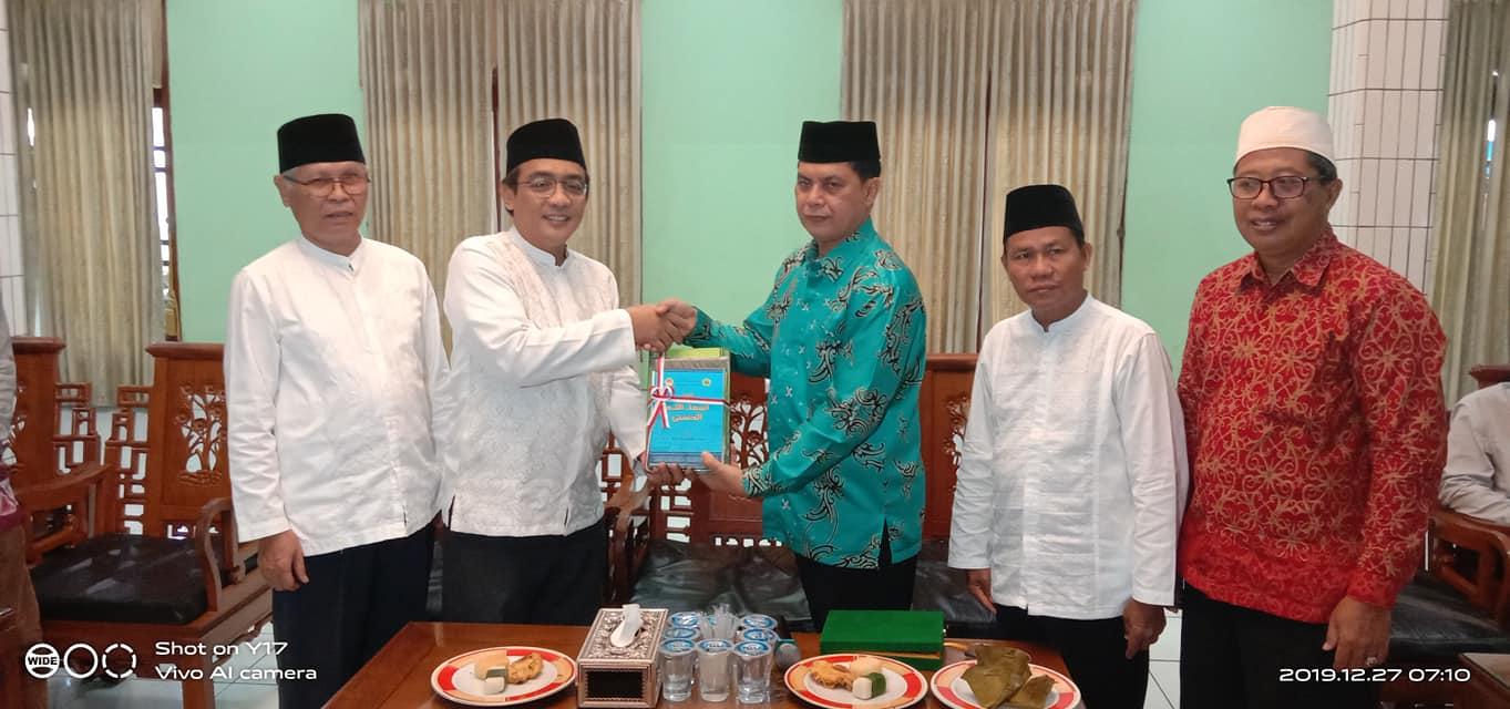 Penyerahan cinderamata batik khas Kalimantan oleh pengurus MUI PPUTimur kepada KH Soenarto MSi. Foto: Nuzuludin