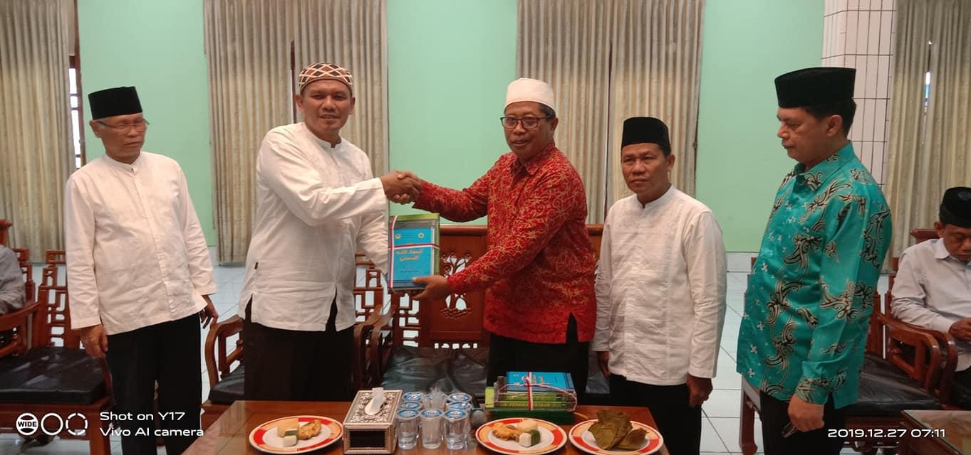 Penyerahan cinderamata batik khas Kalimantan oleh H Nuzuludi Susanto MUI PPUTimur kepada KH Soenarto MSi. Foto: Nuzuludin