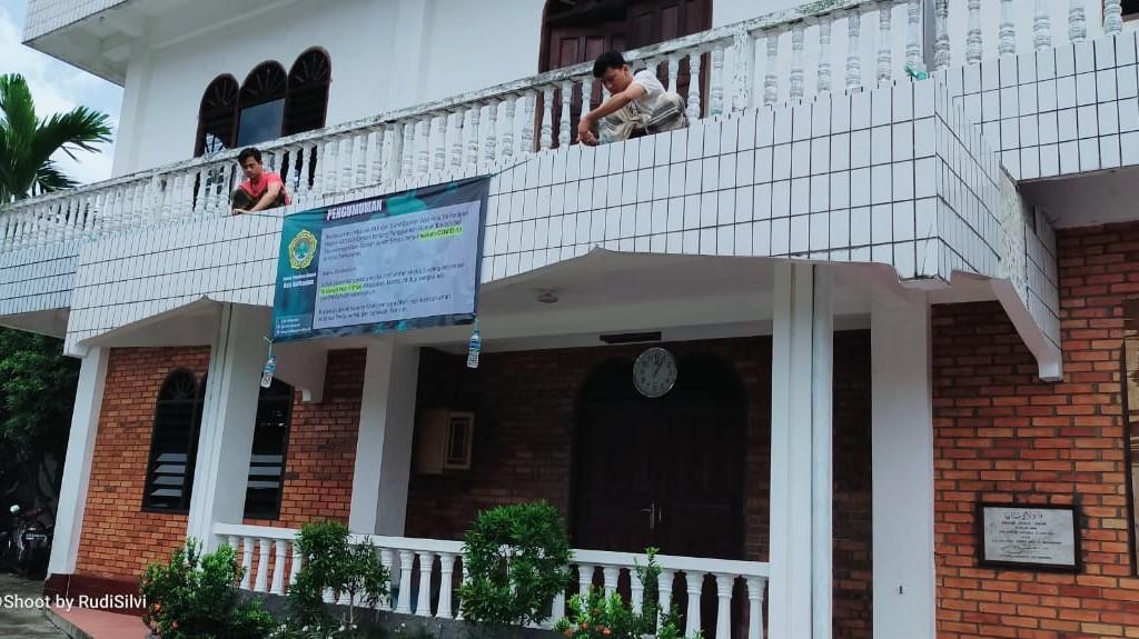 Pemasangan spanduk pengumuman tidak menyelenggarakan Salat Jumat di Masjid Nurul Iman Karang Jawa Balikpapan. Foto: Istimewa